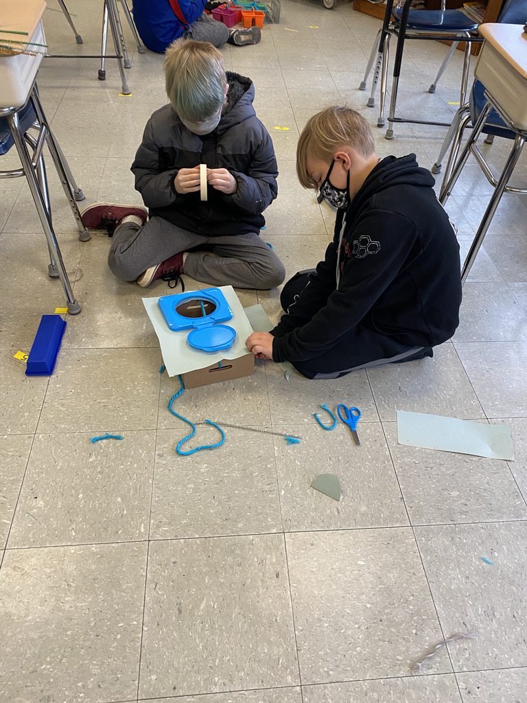 students building leprechaun trap on the floor