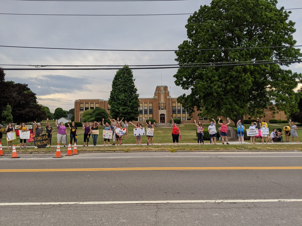 row of teachers waving with elementary school visible in the background
